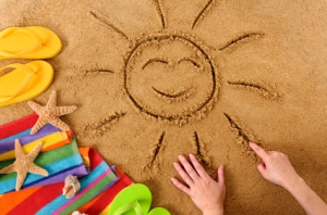 Child drawing a smiling sun on a sandy beach, with beach towel, starfish and flip flops (studio shot - warm color and directional light are intentional).